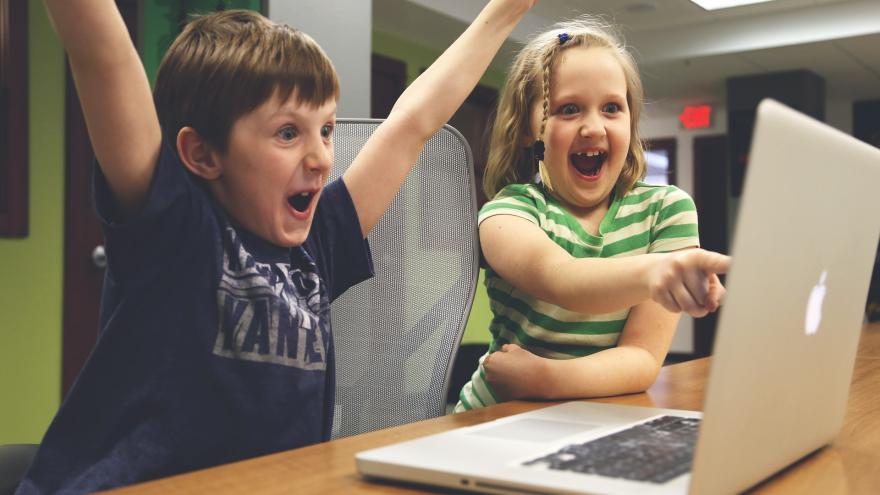 Dos niños felices frente a un ordenador