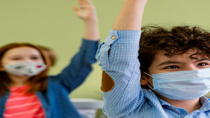 Un niño y una niña en un aula levantando la mano para participar