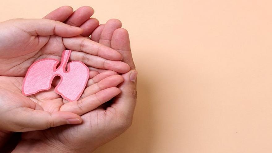 Manos de niño sobre manos de adulto con las palmas hacia arriba sujetando una figura de papel con forma de pulmones