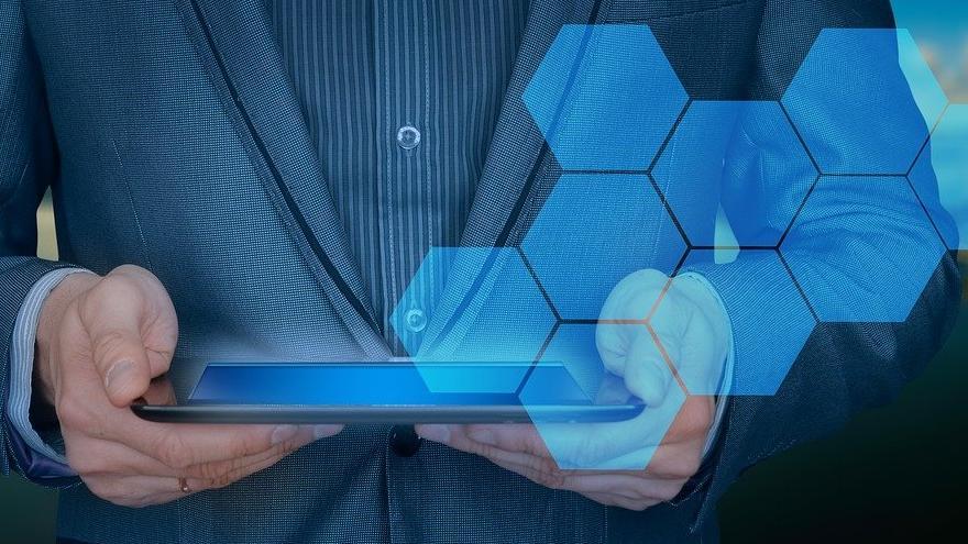 Empresario con una tablet y la silueta de una ciudad al fondo