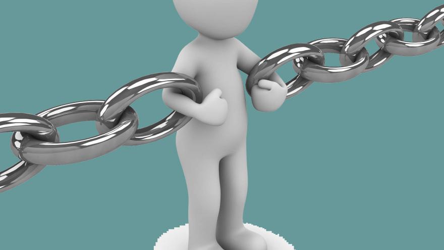 un muñeco de forma humana haciendo de eslabón de una cadena