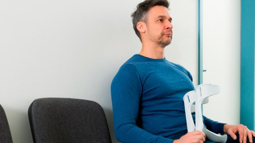 Imagen ilustrativa de un hombre con muletas en una sala de espera