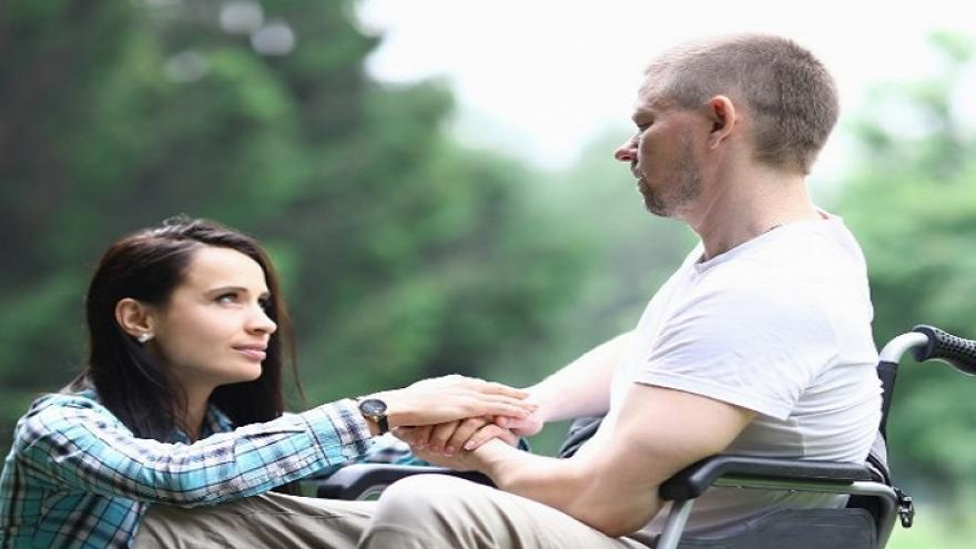 Dos personas mirándose agarradas de la mano, una sentada en el suelo y otra sentada en una silla de ruedas