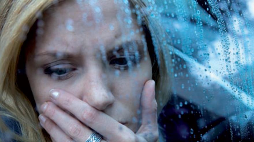 foto de una mujer con mirada triste en un día lluvioso