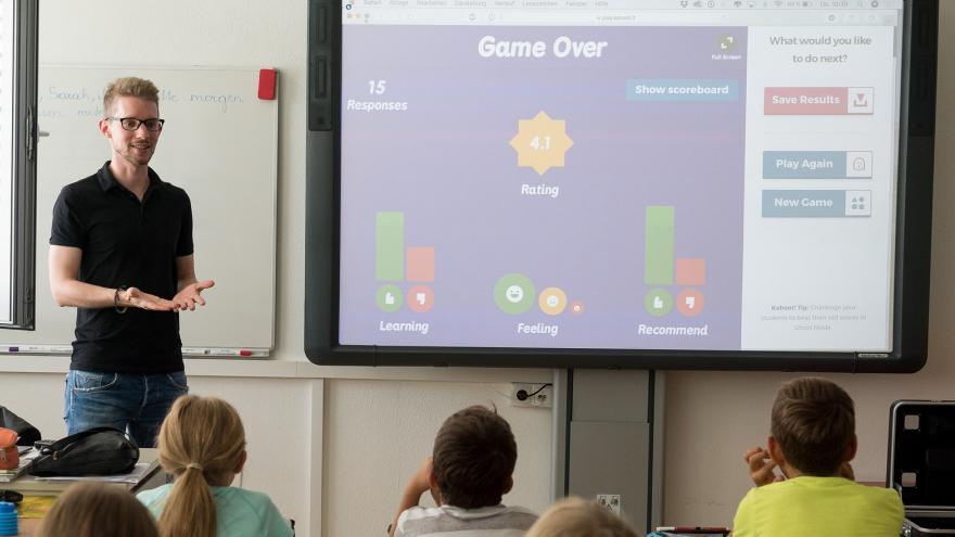 Profesor explica a los alumnos con ayuda de una pizarra digital