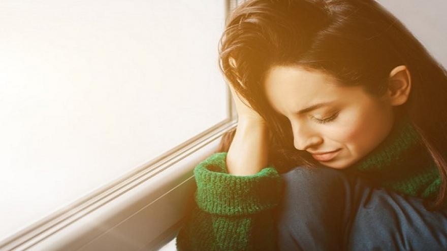 Mujer con la cabeza agachada apoyada en su mano y los ojos cerrados