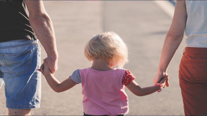 Hombre y mujer dando una mano cada uno a un niño