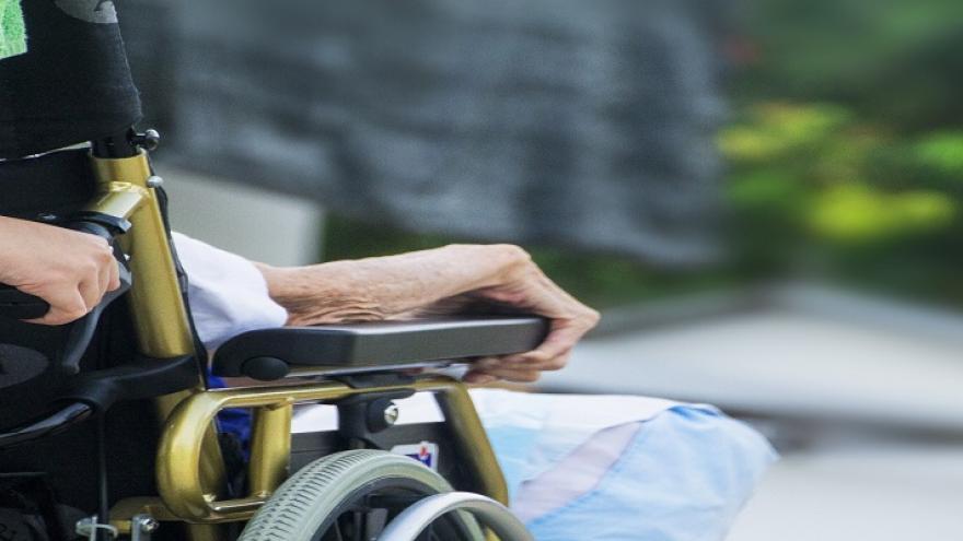 Mano de anciano apoyada en silla de ruedas empujada por mano de persona más joven