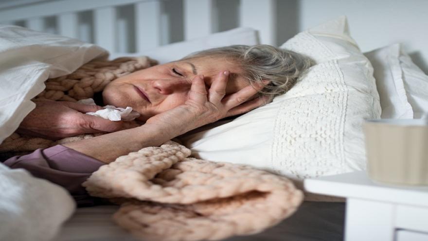Señora mayor tumbada en la cama arropada