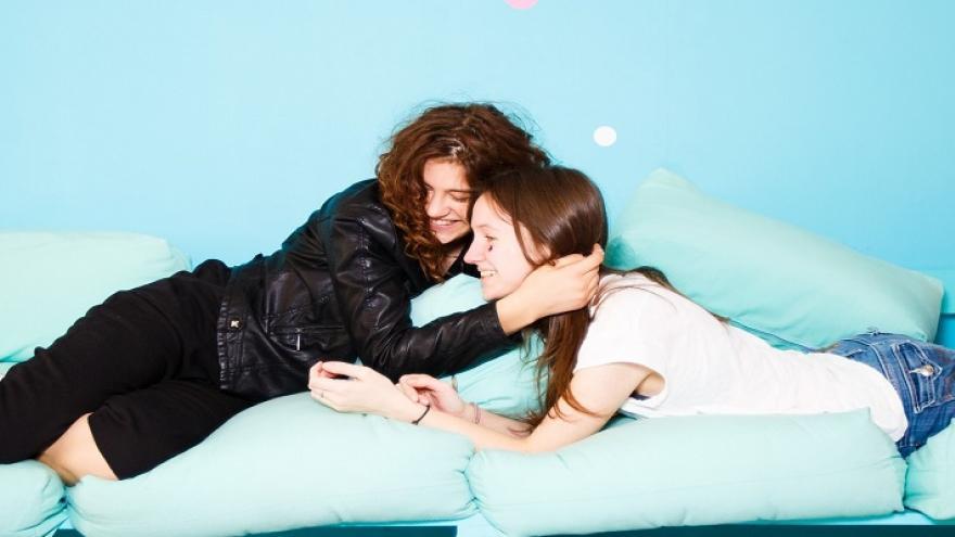 Dos jóvenes tumbadas en un sillón sonriendo y abrazadas