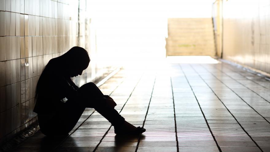 joven con capucha sentado en el suelo