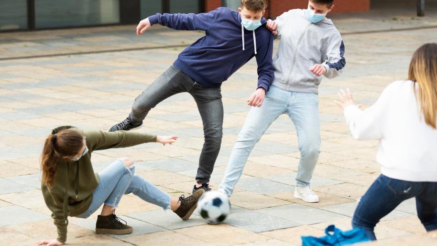 Jóvenes jugando al fútbol con mascarillas
