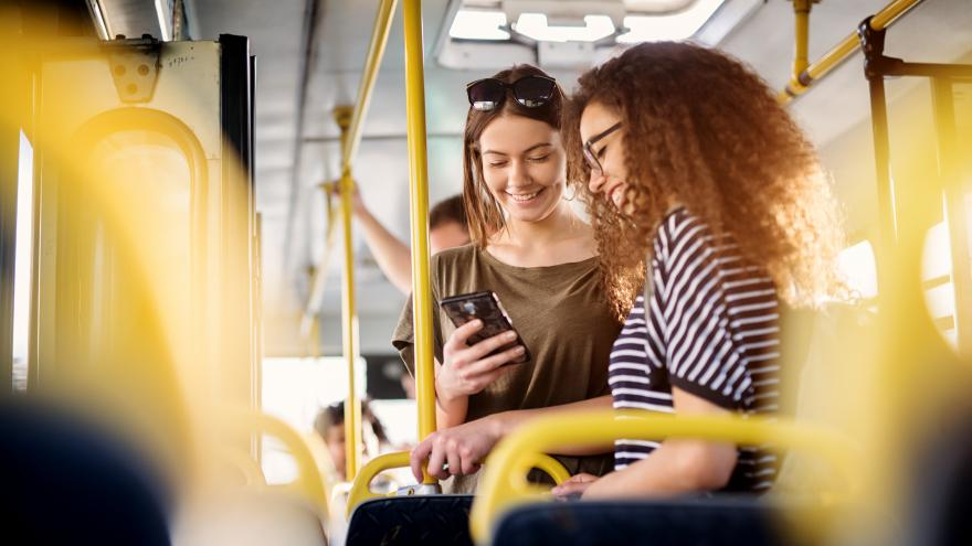 Jóvenes en el autobús mirando el móvil