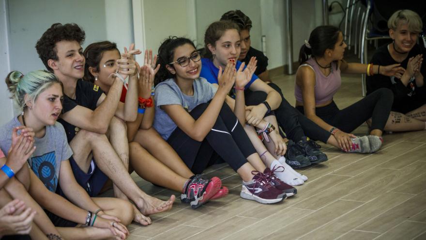 Jóvenes sentados en el suelo aplaudiendo