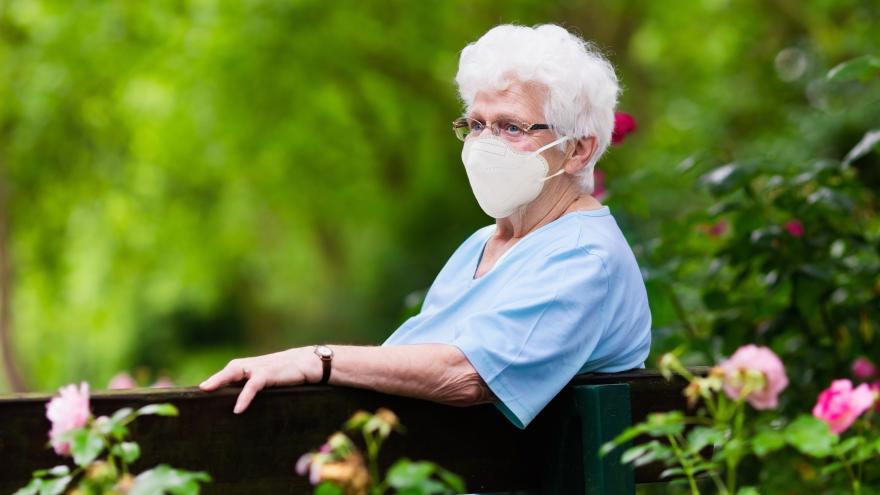 Anciana sentada con mascarilla FFP2