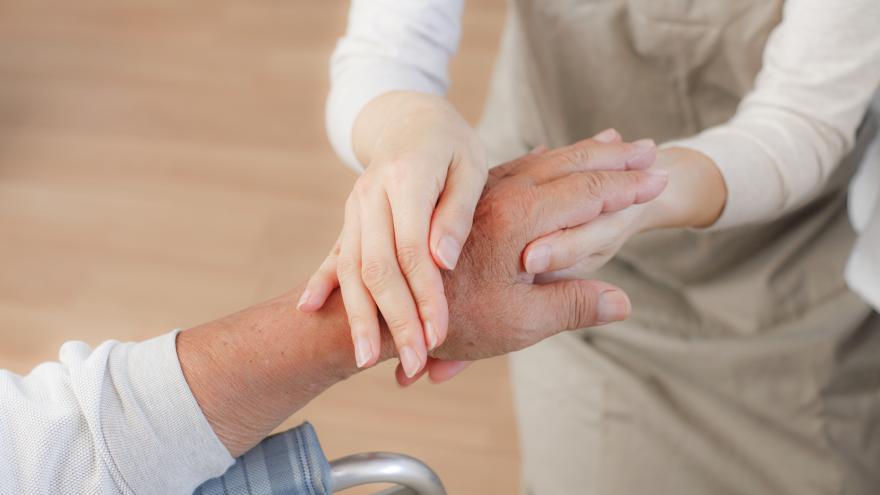 Mano de persona mayor siendo agarrada por otra