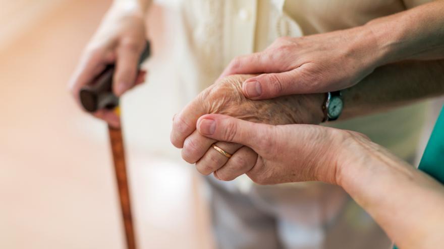 Manos de una persona joven cogiendo las de una persona mayor que en la otra mano tiene un bastón