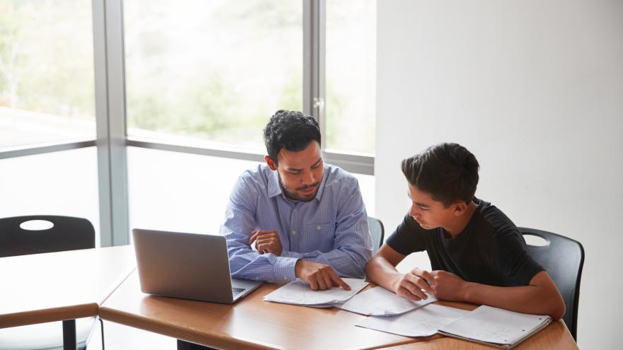 PErsona adulta y un adolescente sentados en una mesa mirando unos cuadernos