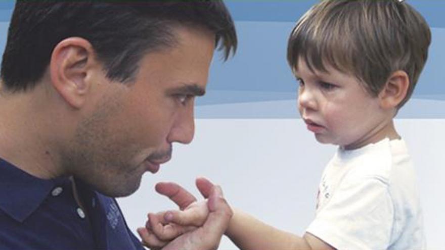 Padre soplando la herida de la mano de su hijo
