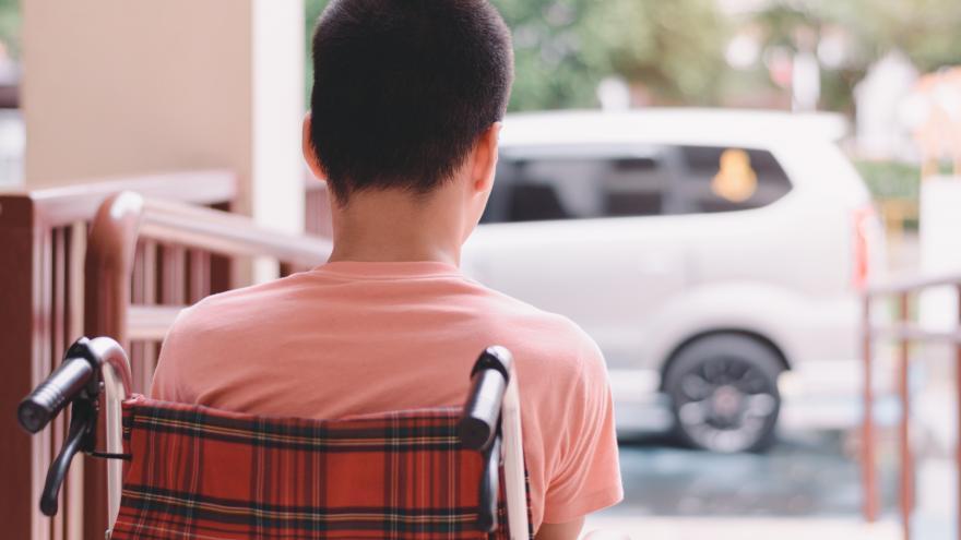 Niño de espaldas en silla de ruedas