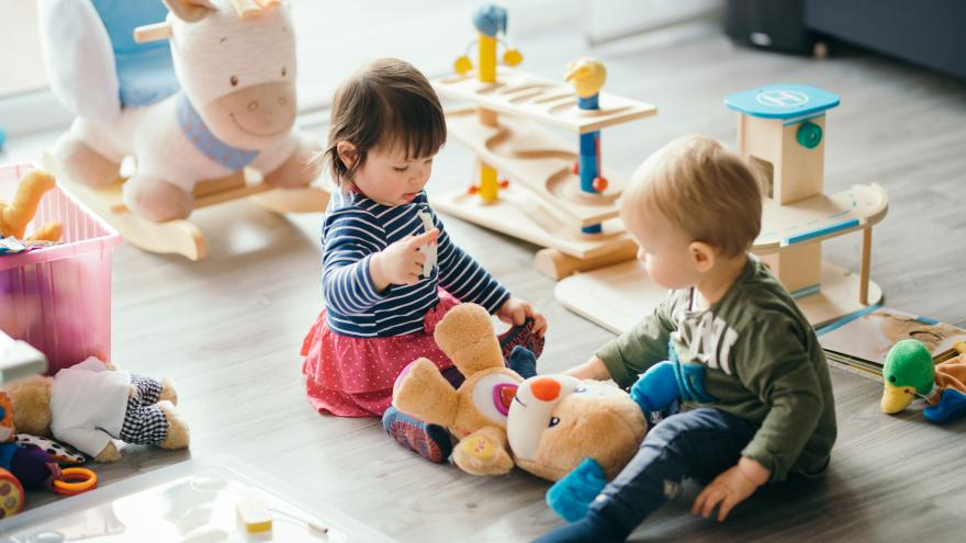 Un niño y una niña jugando en el suelo
