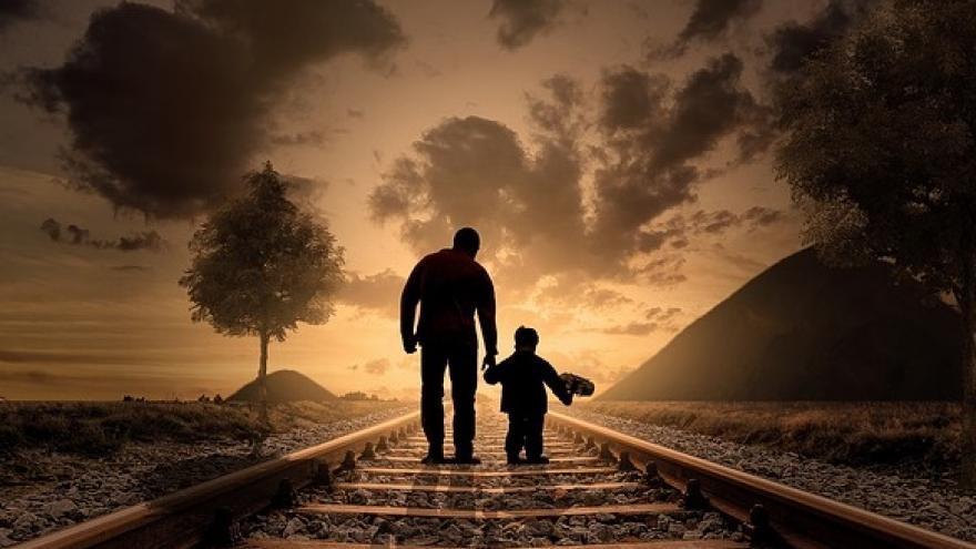 Padre e hijo pequeño caminando por unas vías de tren