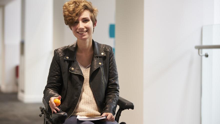 Imagen ilustrativa de una joven en silla de ruedas con una carpeta de información