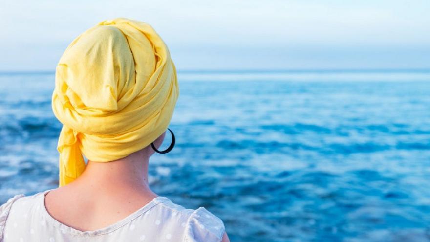 Imagen de mujer mirando al mar con pañuelo amarillo en la cabeza