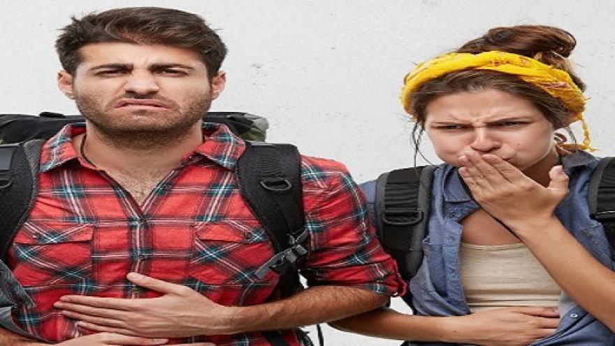 Un chico y una chica con mochilas y gestos de malestar gástrico