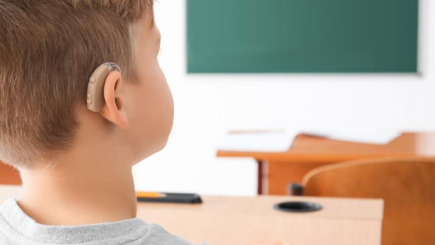 Un niño con un audífono en clase