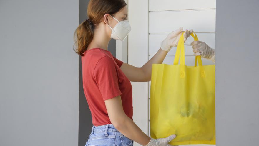 Mujer solidaria entregando bolsa con comida COVID