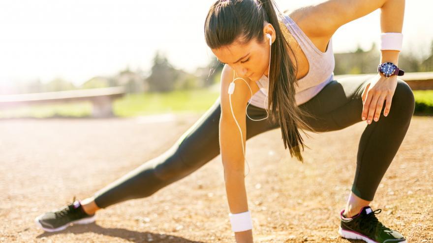 Una joven estirando antes de hacer deporte