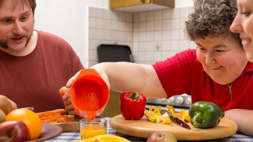Tres personas con discapacidad desayunando