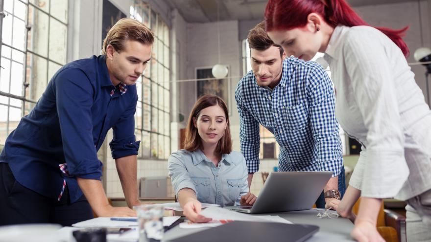 Equipo de jóvenes trabajando alrededor de una mesa con ordenador