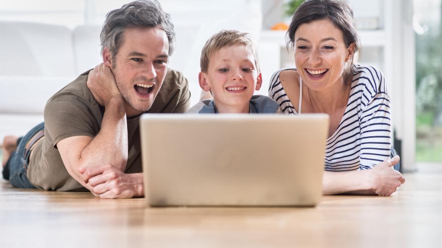 Una familia sonríe frente al ordenador