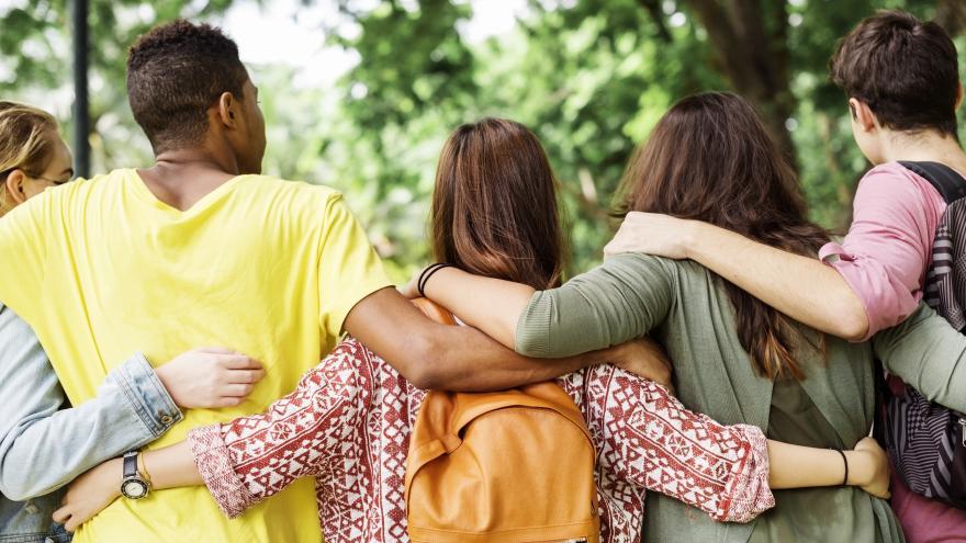 Varios jóvenes de espaldas abrazados