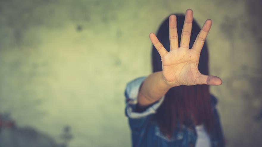 Imagen de una mujer con la mano extendida y alzada