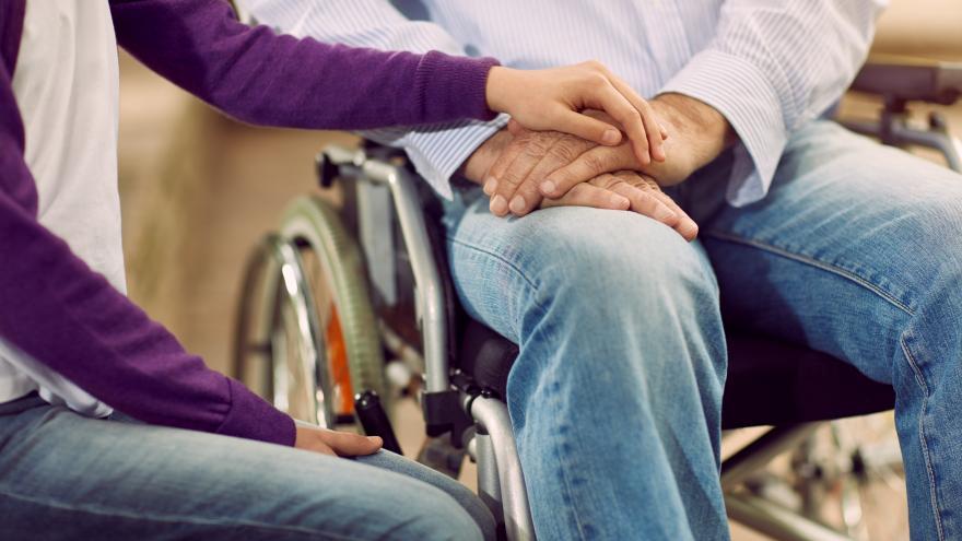 Una mujer pone sus manos sobre las de un hombre que está en una silla de ruedas