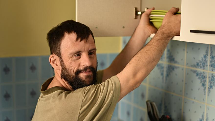 Un joven con síndrome de Down coge unos platos de un armario en la pared