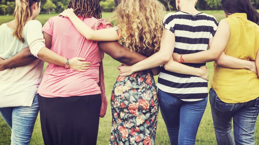 Varias mujeres de espaldas en línea abrazadas por la cintura