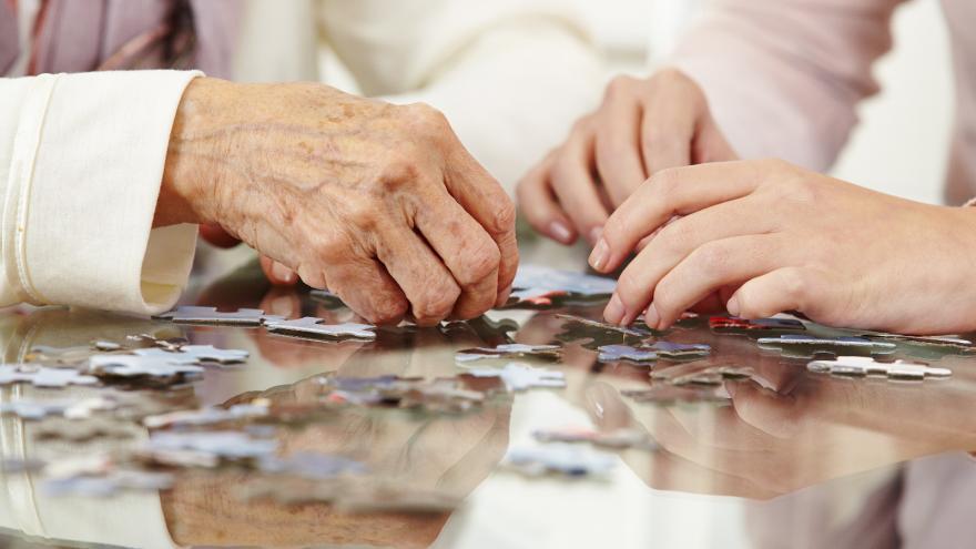 Manos de una persona mayor resolviendo un puzzle en una residencia