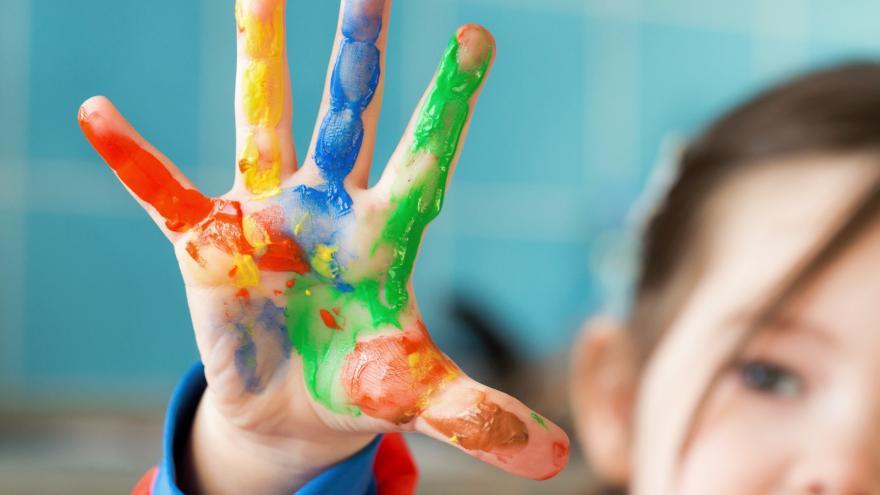 Niña en colegio con las manos de pintura