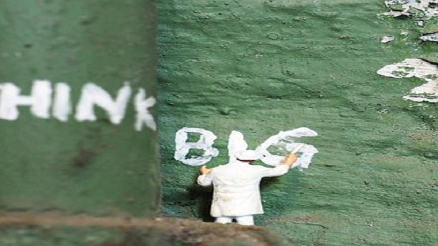 """hombre escribiendo en un muro verde las palabras en inglés """"piensa en grande"""""""