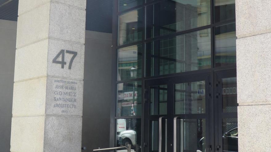 puerta de entrada al edificio de la sede central del IMIDRA en la calle Leganitos nº 47 de Madrid, puerta metálica con listones negros con espejos