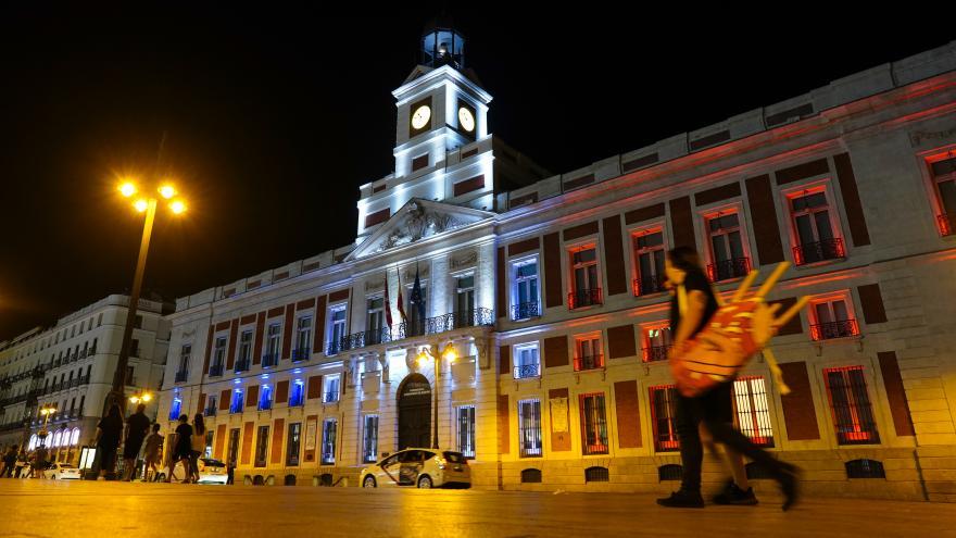 Una vista de la Real Casa de Correos iluminada con los colores de su bandera nacional