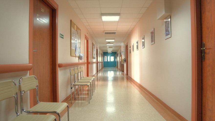 Imagen de un pasillo iluminado con sillas y cuadros