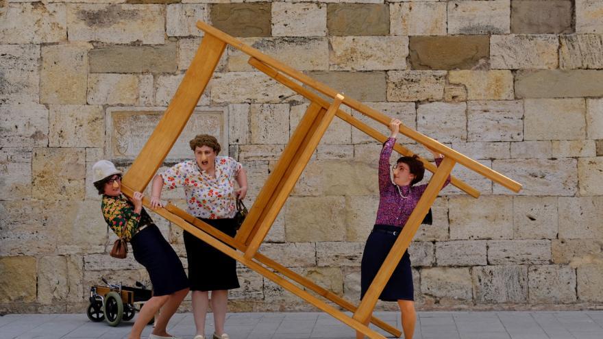 Las actrices sujetando una silla gigante
