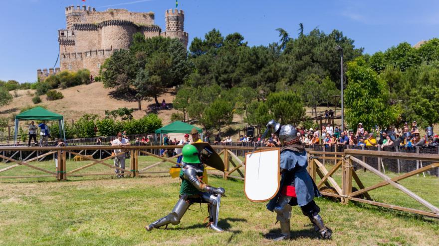 Dos guerreros medievales luchando con el castillo de fondo