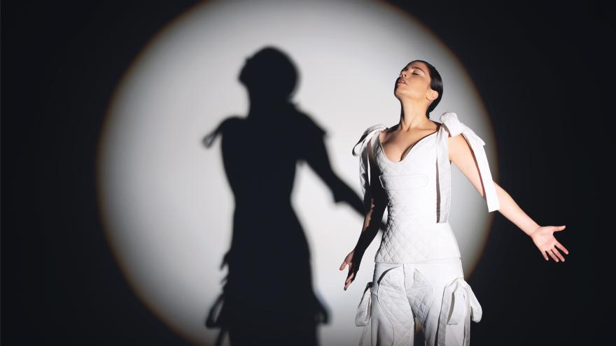 Bailarina en pose con brazos abiertos vestida de blanco