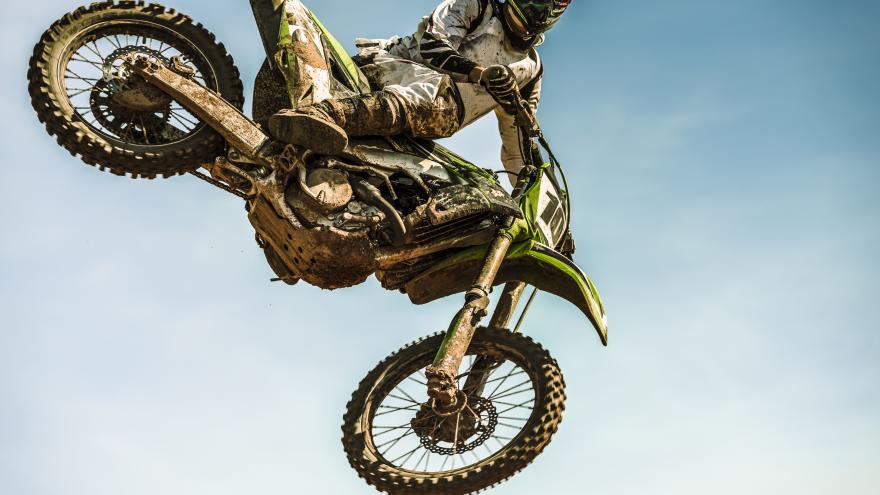 Piloto de motocross saltando con la motocicleta